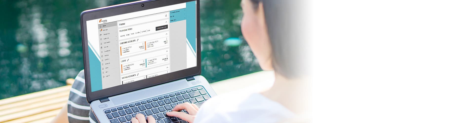 woman sitting on dock using laptop and looking at digital banking