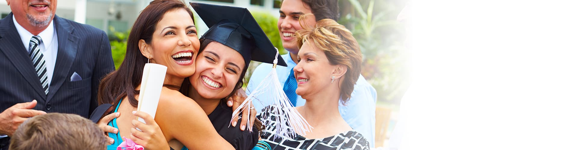 Woman hugging daughter who is wearing a cap and gown and holding her diploma