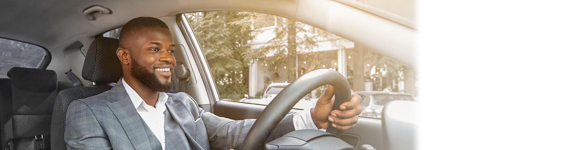 Man wearing gray suit driving car
