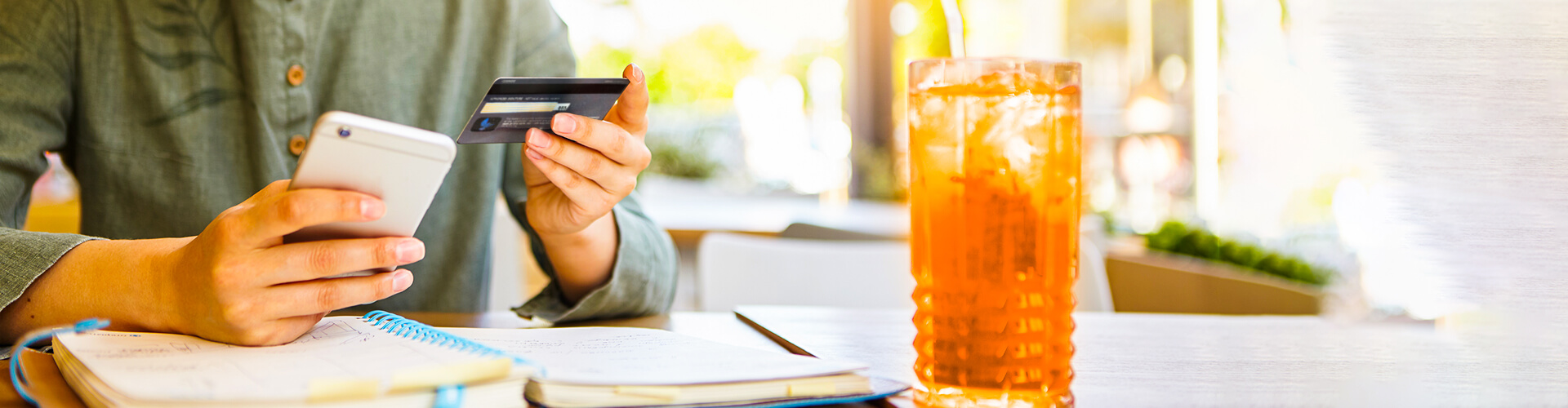 Person holding smartphone in one hand and Ascentra credit card in other. Hand holding smartphone is resting on a notebook. Person is wearing a green shirt