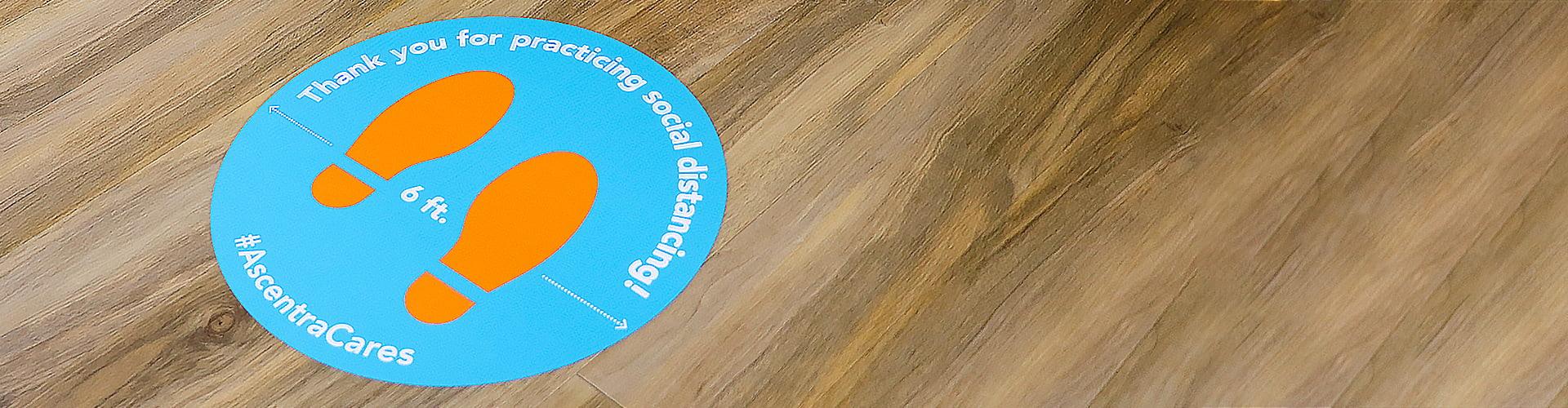 Blue circle on hard wood floor with orange foot prints