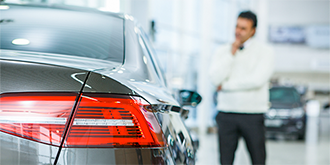 Man standing next to car in dealership