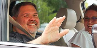 Dale smiling and waving out the window of his car. His wife Angie in the passenger seat smiling at Dale.