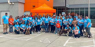 Group of Ascentra staff standing in front of orange building wearing blue shirts