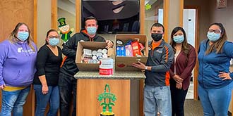 Ascentra Muscatine branch holding up 2 cardboard boxes of the food they collected during the food drive.