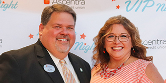 Dale and Angie Owen standing in front of Ascentra VIP night backdrop