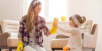 Mother and daughter high fiving. Mother wearing yellow gloves and flannel shirt