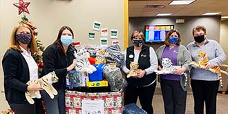 Ascentra Clinton South 14th branch standing in front of a holiday network toy box overflowing with toys. All the ladies are holding stuffed tigers that were donated.