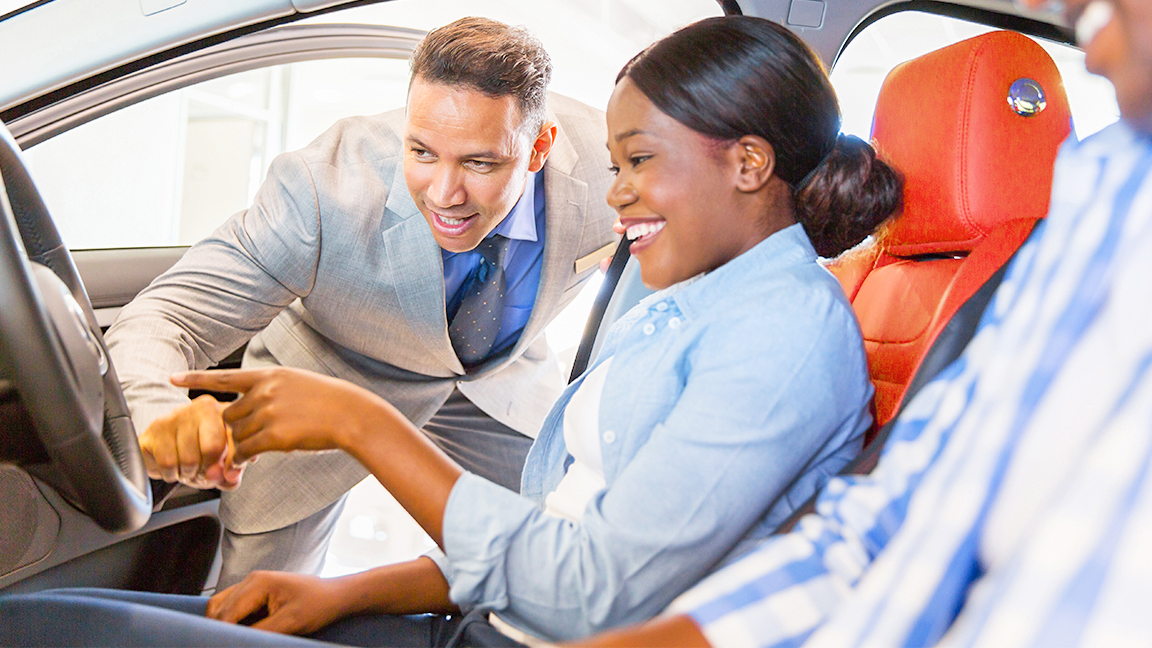 Woman being showed car features by salesman