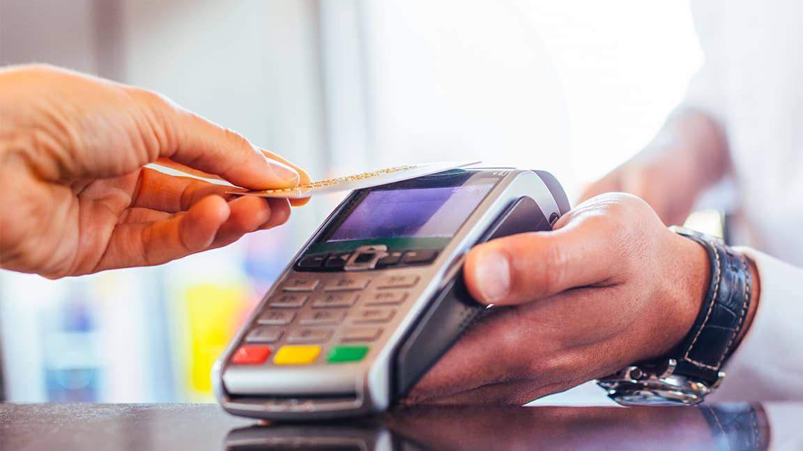 Consumer tapping credit card to pay