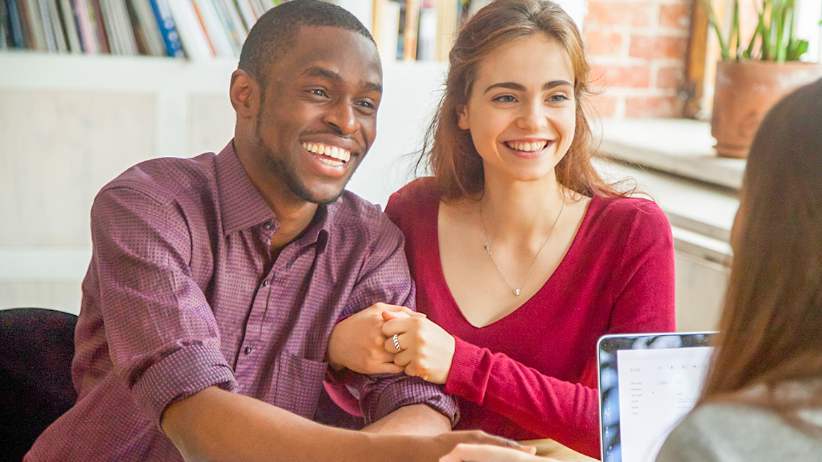 Happy couple sitting with loan officer