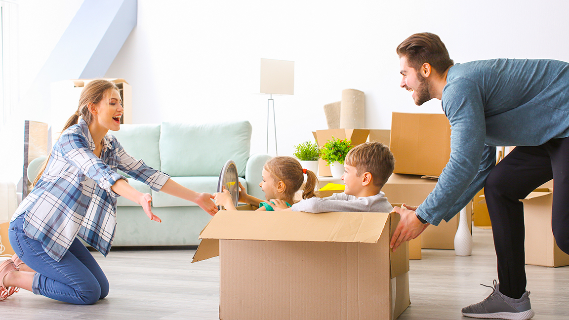 Parents playing with kids in moving boxes