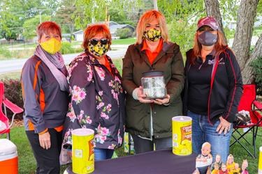 Group of ladies in masks standing behind lemonade stand