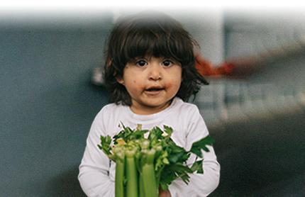 Little girl holding celery