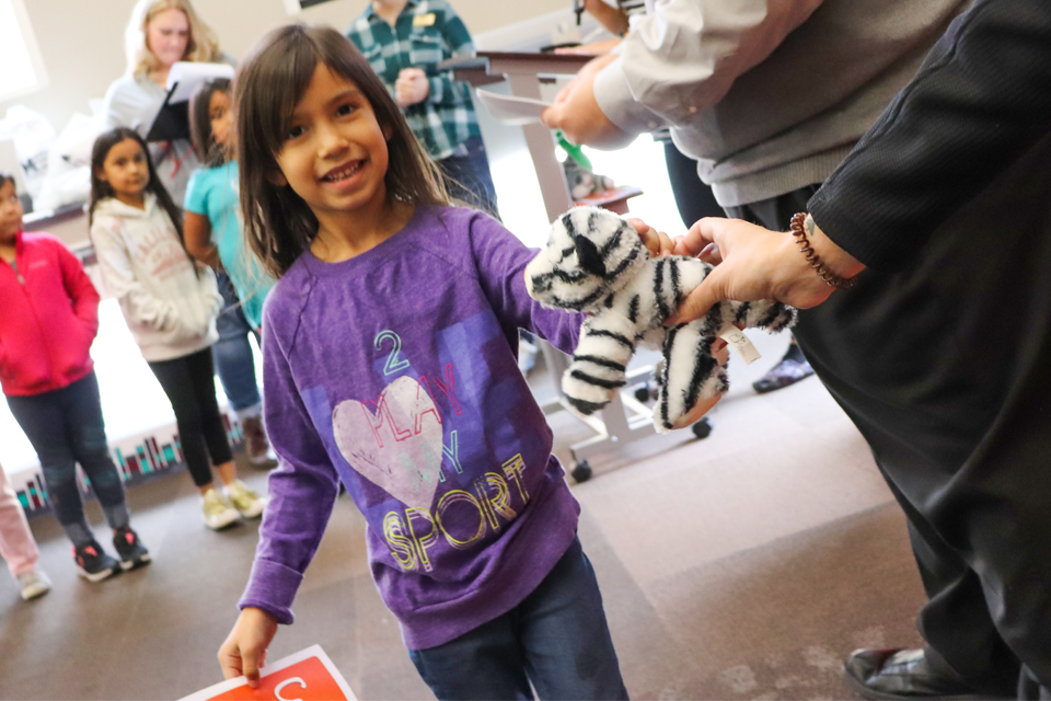Girl is handed stuffed tiger.